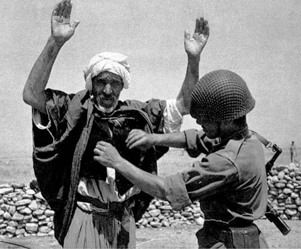 Un veil est contrôlé et fouillé par un militaire pendant la guerre d'Algérie.